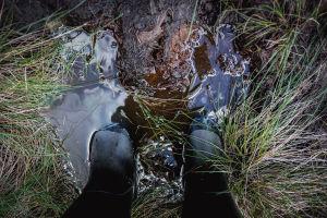 Mustat saappaat märässä suossa, osittain suoveden peitossa, kuvattuna ylhäältä päin.
