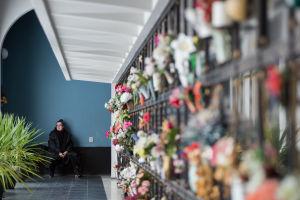 Nainen istuu uurnaholvissa Hietaniemen hautausmaalla.