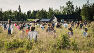 Heinäseipäistä ja turpeesta tehtyjä Hiljainen kansa -teoksen hahmoja pellolla Suomussalmella, taustalla valtatie 5 ja Niittykahvila.
