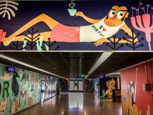 Myyrmäen juna-asemalla seinämaalaus, jossa loikoilee mieshahmo, jolla paita jossa teksti I love Myrtsi.