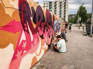 Graffitiseinällä ihmisiä maalaamassa.