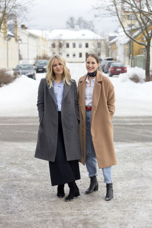 Två kvinnor står ute på en gata. Michelle till vänster i bild har långt blont hår och grå kappa. Sandra till höger har håret i hästsvans och beige kappa. Båda ler.