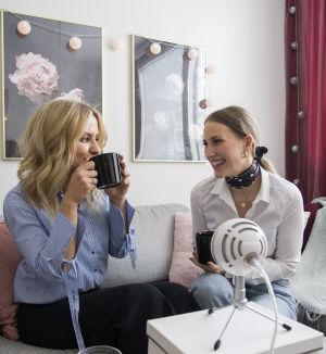 Två kvinnor sitter i en soffa och dricker te och skrattar. Framför sig har de en stor mikrofon eftersom de just spelat in en podcast.