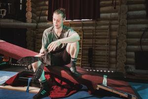 Sirkustaiteilija istuu keinulaudalla, kädessä pupunkorvat.