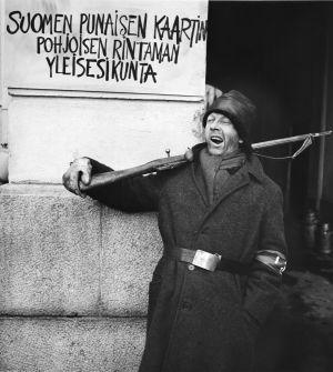 """Tunnistamaton näyttelijä. Seinässä teksti """"Suomen punaisen kaartin Pohjoisen rintaman yleisesikunta"""" tv-draamassa Lennu (1967)."""