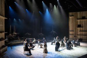 Lahden kaupunginteatterin näyttelijät lavalla: kukin istuu tuolillaan hiljaa.