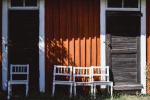 Valkoisia tuoleja, taustalla punainen puutalon seinä