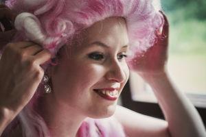 En leende kvinna med peruk.