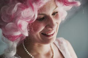 En skådespelare med peruk och halsband ler.
