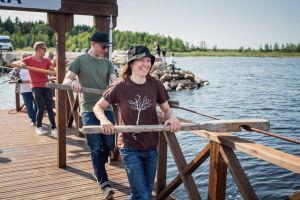 Tanja Råman, Rasmus Tåg ja Nicke Aldén vetävät kapulalossin kapuloilla vaijeria taaksepäin, ylitetään salmea Varjakassa Oulussa.