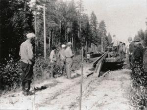 Mustavalkoisessa arkistokuvassa työmiehiä metsässä purkamassa junarataa.