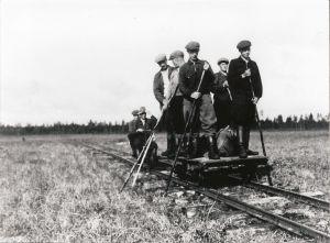 Mustavalkoisessa arkistokuvassa työmiehiä resiinan päällä kapearaiteisella raiteella.