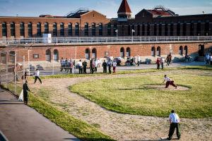 Ett tjugotal intagna står på motionsgården i Atticafängelset i USA. Några av de intagna spelar softball.