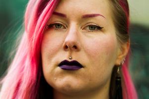 Pinkkihiuksinen vahvasti meikattu Karoliina Korppoo katsoo suoraan kohti kameraa.