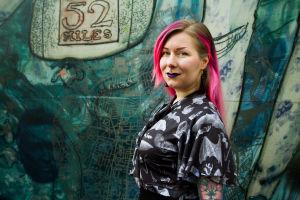 Pinkkihiuksinen Karoliina Korppoo graffitiseinän edessä.