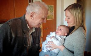 Pehr-Eric Nyman ser på sitt barnbarnsbarn som ligger i sin mammas famn