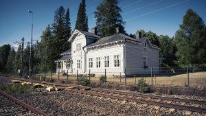 Vaalea vanha puinen rautatieasema kuvattuna radan takaa, aseman takana korkeita havu- ja lehtipuita.