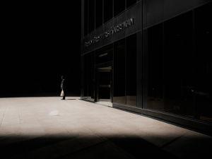 Mies seisoo muovikassin kanssa tummanpuhuvan rakennuksen edessä.