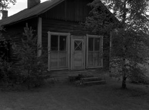 Mustavalkoisessa arkistokuvassa huonokuntoinen puutalo.