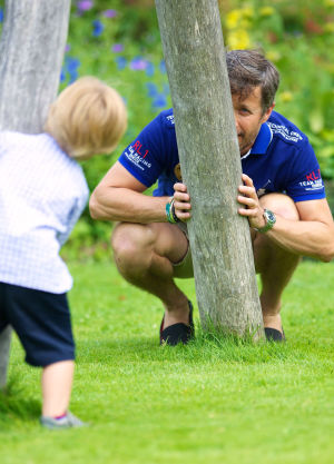 Man leker med liten pojke, gömmer sig bakom träd