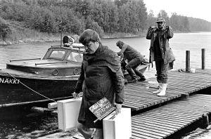 Kameramies Hannu Järveläinen, äänisuunnittelija Eino Lehtinen ja kuvaussuunnittelija Mauri Aalto tulossa veneellä kuvauspaikalle (1977).