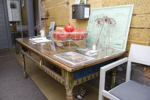 Ett gammalt träbord. Står i en hall. På bordet står en fruktskål, en karta, blommor och en gästbok.