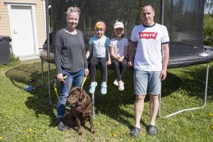 En kvinna, två barn (flickor) och en man står framför en stor studsmatta. Framför dem sitter en brun labrador. Det är sommar och solen skiner.
