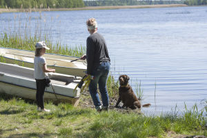 En kvinna, en flicka och en hund står på en strand. Kvinnan står i beredskap för att kasta en pinne som hunden kan hämta.