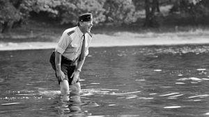 Artturi Reinikainen eli näyttelijä Tenho Saurén seisoo vedessä polviaan myöden. Hän irvistää, vesi on kylmää.