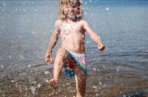 En flicka som plaskar i vattnet på en strand.