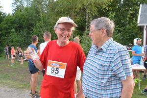 Två män på ett löpevenemang står och skrattar