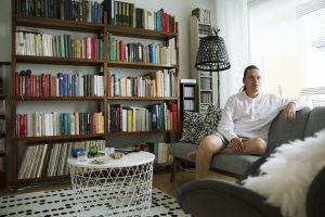 Kasper sitter i en soffa som står framför en stor bokhylla.