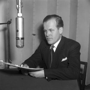 Eero Saarenheimo istuu pöydän ääressä 1955 ja lukee tekstiä.