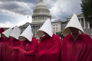 Women dressed as handmaids demonstrated against funding cuts to Planned Parenthood outside the National Capitol in Washington