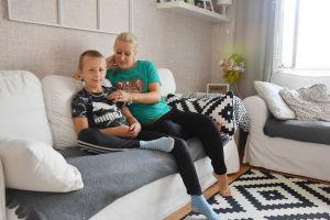 En bild på en pojke och en kvinna som sitter i soffa. Kvinnan är pojkens mamma och rättar till pojkens t-skjorta. De sitter i en vit soffa i ett vardagsrum.