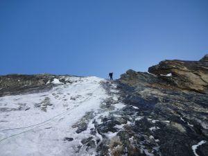 En person står uppe på en bergstopp. Nedanför personen hänger ett rep. Hen ska snart börja gå ner för berget med hjälp av repet.