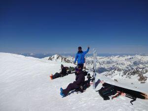 Tre personer sitter uppe på en bergstopp. De har med sig skidor. En person vinkar till fotografen.