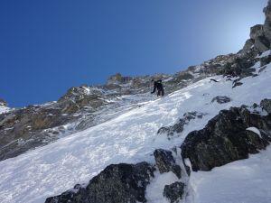 En skidåkare står högt upp på ett brant berg, redo att börja åka utför.