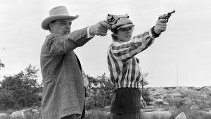 Tenho Saurénin näyttelemä Mr Blink sekä Kari Kihlströmin näyttelemä Arpinaama osoittavat aseilla kuvan oikeaan reunaan.