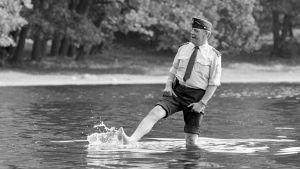 Artturi Reinikainen eli näyttelijä Tenho Saurén seisoo vedessä ja potkii vettä.