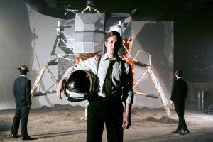Matt Johnson pitelee astronautin kypärää, taustalla kuumoduli ja CIA:n agentteja, elokuvassa Operaatio Avalanche