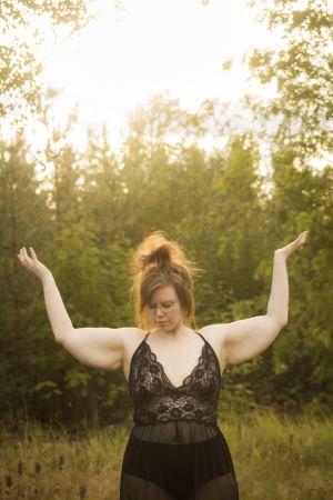 En kvinna iklädd ett nattlinne av svart spets. Hon står på en dimmig äng och i bakgrunden syns skog. Hon håller ut sina armar och tittar ner i marken.