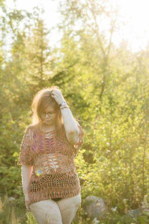 En kvinna iklädd underkläder och en glest virkad tröja. Hon står i en dimmig skog och solen lyser från ena hörnet. Hon tittar ner i marken.
