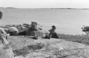 Karvakuonot automatkalla -sarjan kuvauksia 1982. Kuvaussihteeri Kristiina Karhu on suojannut nenänäsä auringolta paperinpalalla, rantakallioilla myös näyttelijä Kalevi Honkanen sekä Karvakuonojen Riku ja Eno-Elmeri.