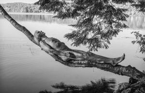 Kuvassa puu, alaston mies ja vesistö.