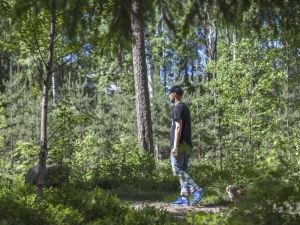 Mikko Toivianen Lyyli-koiran kanssa metsässä.