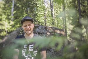 Mikko Toiviainen luonnossa, istuu ison kiven edessä.