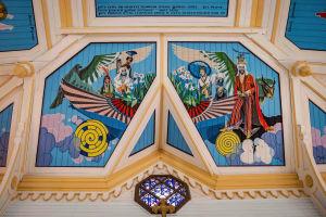 Alttaritaulu, johon maalattu kirkkain värein Jeesus, eri etnisiä ryhmiä edustavia enkeleitä, papukaija, pilviä