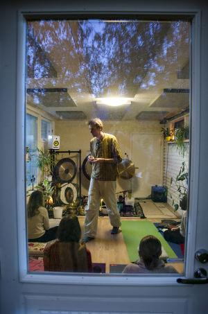 Stefan Backas förbereder ljudbadet. Vi ser deltagarna genom en dörr.