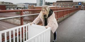 Tyttö työntää pinnasänkyä sillalla.